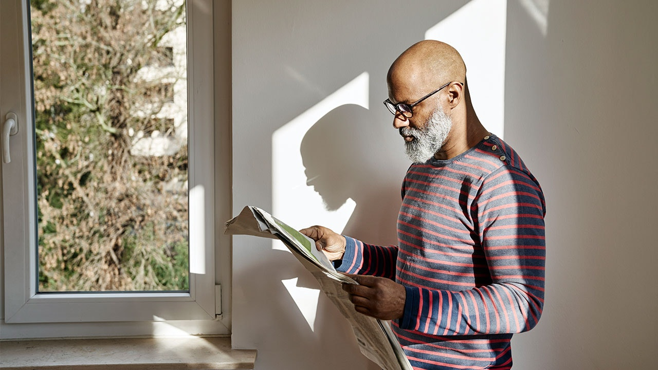 Man reading newspaper in his home