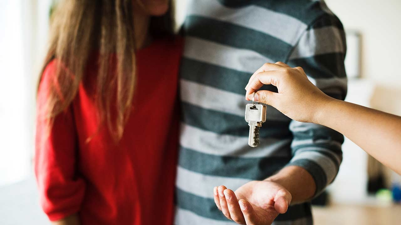 A couple picking up the keys to their new property