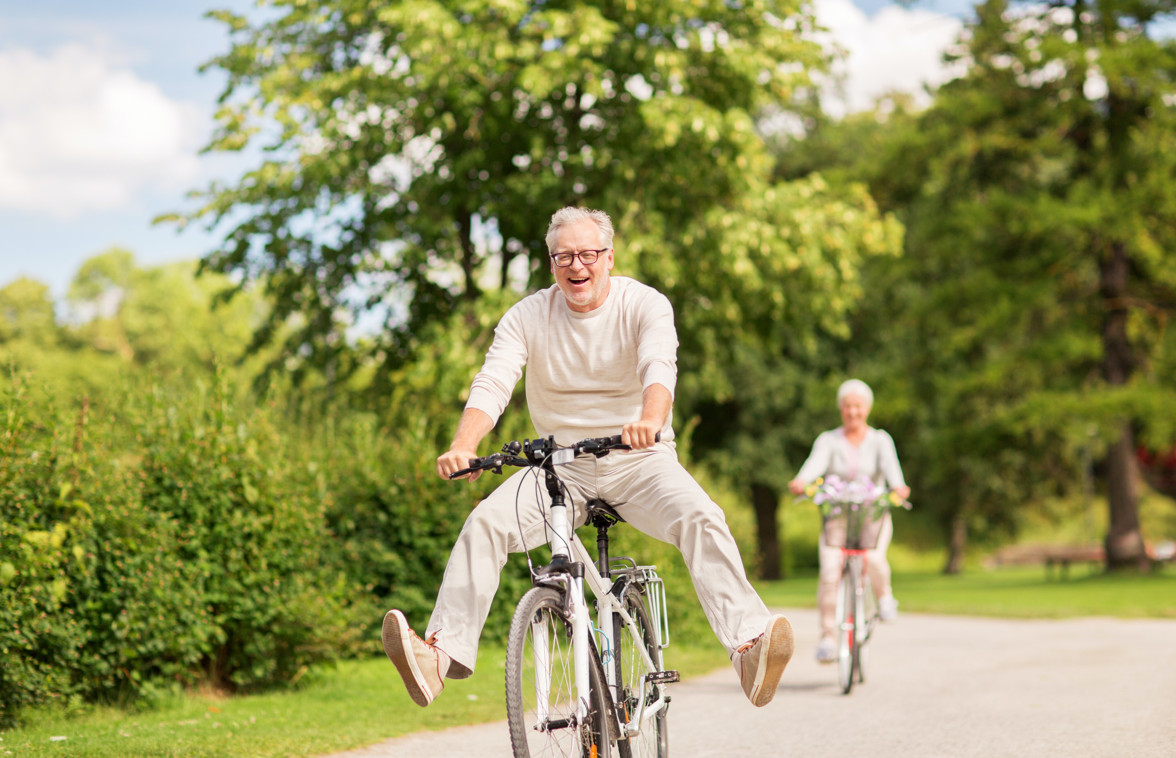 Older over 50s couple riding bikes happily through a park