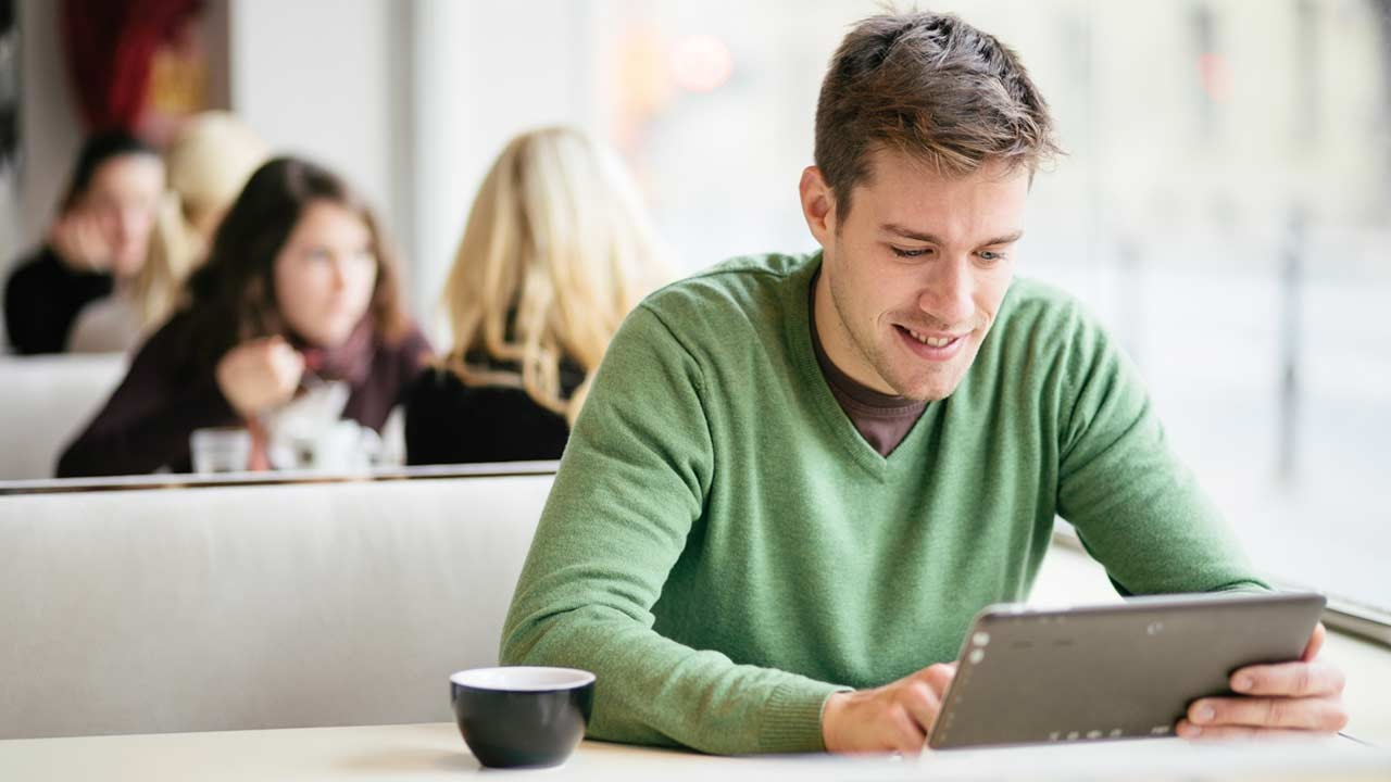 Man happily looking at his tablet
