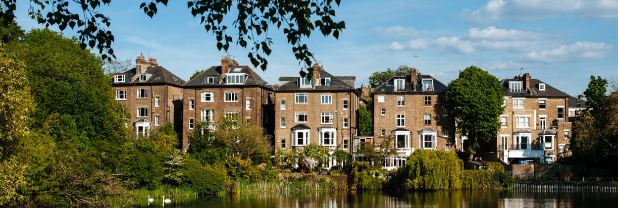 Image of 4 storey houses by a lake