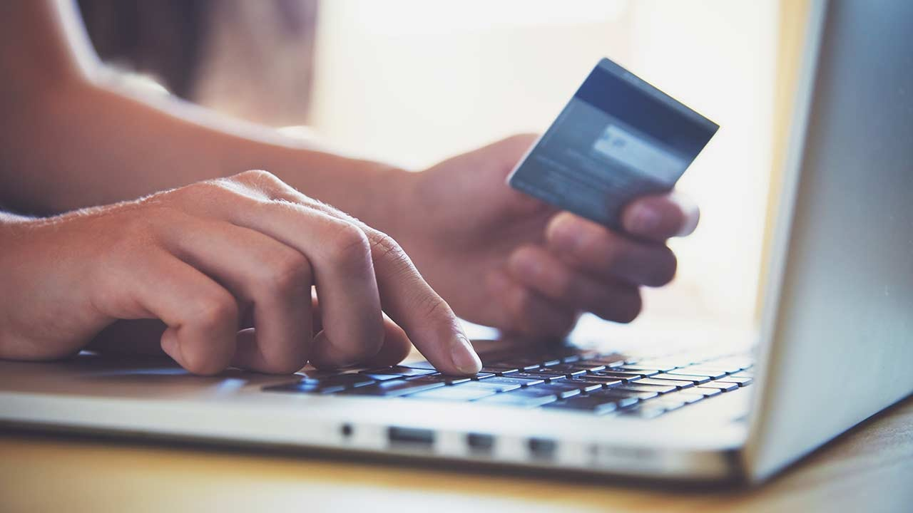 Person paying for goods and services online with a card