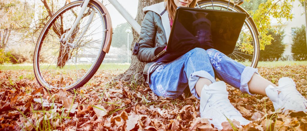 Girl studying outside among leaves with laptop and bike