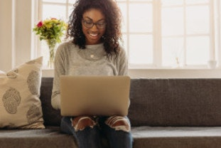 Happy woman using laptop to compare energy prices.