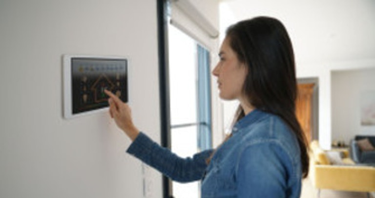A woman operating a smart thermostat