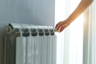 Woman with new energy supplier adjusting temperature on radiator