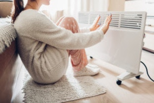 Woman warming herself next to heater