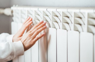A woman warming her hands on a radiator using kWh