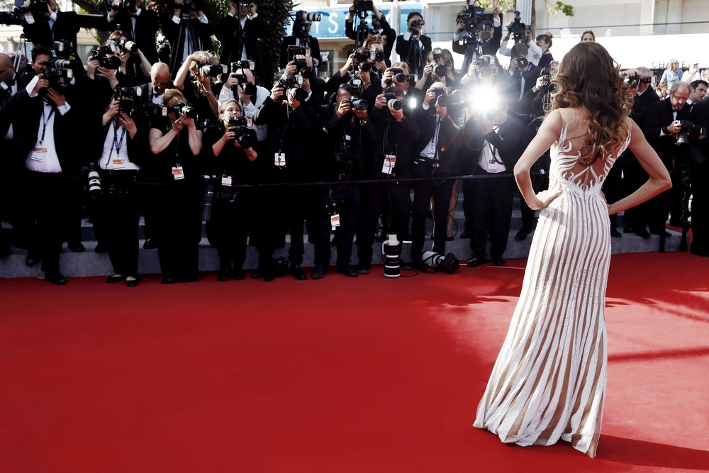 Woman posing in front of cameras at red carpet event