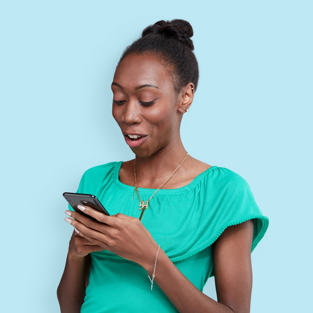 Woman pleasantly surprised holding a phone