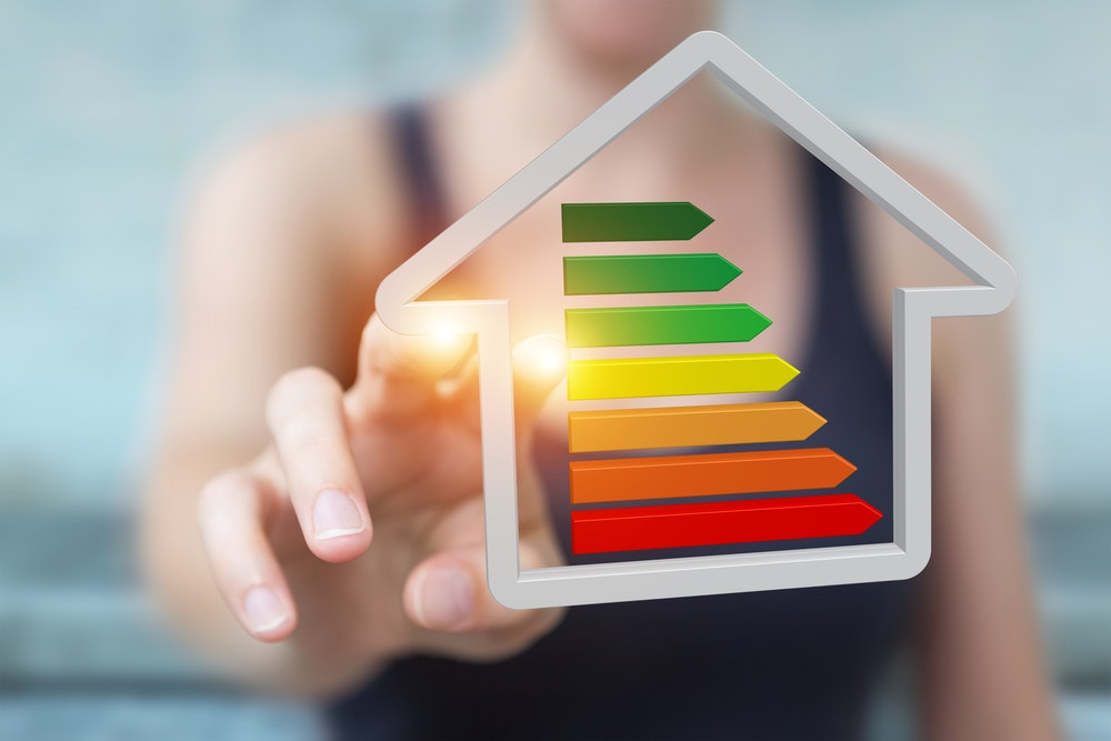 Woman touching house picture with EPC rating.