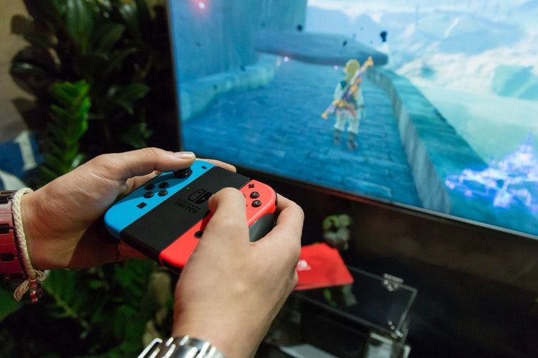 Closeup of someone holding Nintendo Switch controller and playing Zelda on television