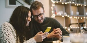 Couple in coffee shop using mobile phone