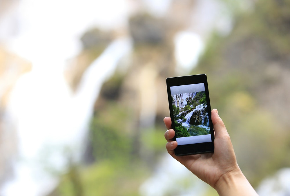 Smart phone taking a photo of a waterfall in the background