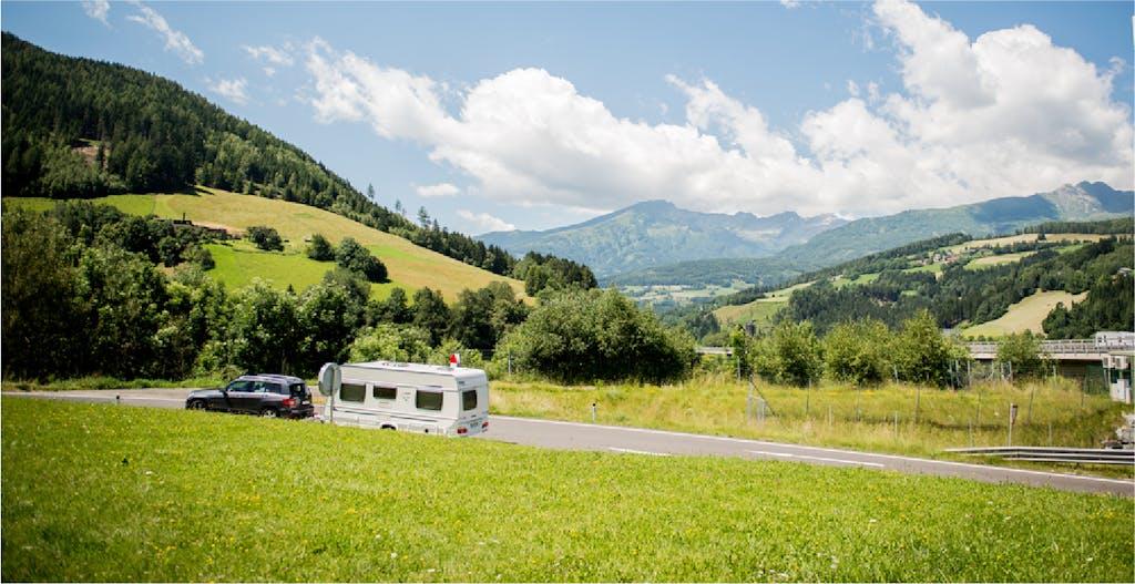 Caravan being toed against a stretch of land, landscape rolling hills