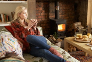 Woman using stove thanks to Winter Fuel Allowance