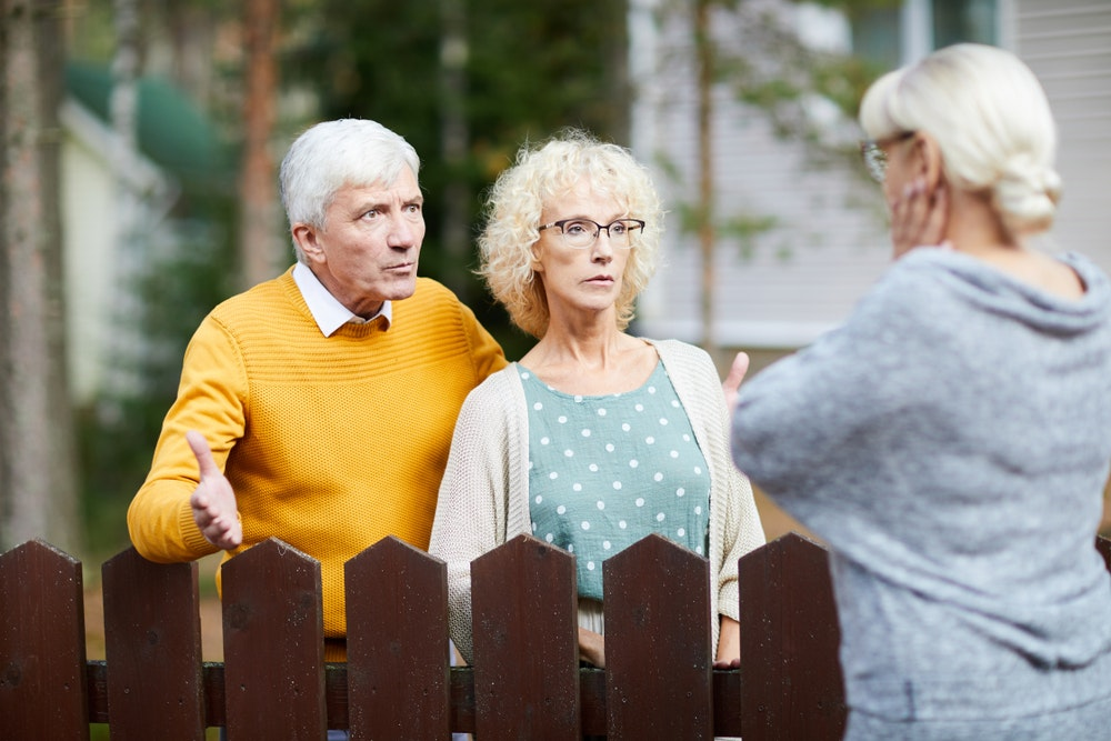 Neighbours disagreeing with each other over a garden fence