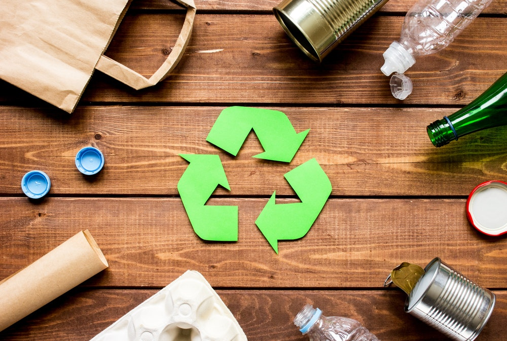 Recycling symbol and recyclable items on desk