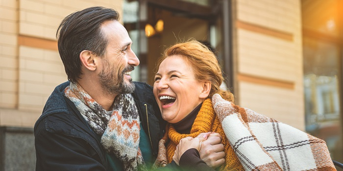 Man and woman laughing outside together, looking comfortable and happy
