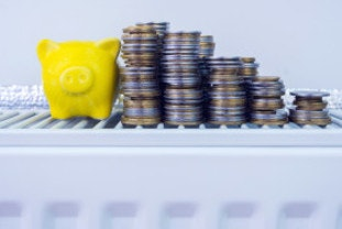 Piggybank and pile of coins on radiator symbolising cheap energy