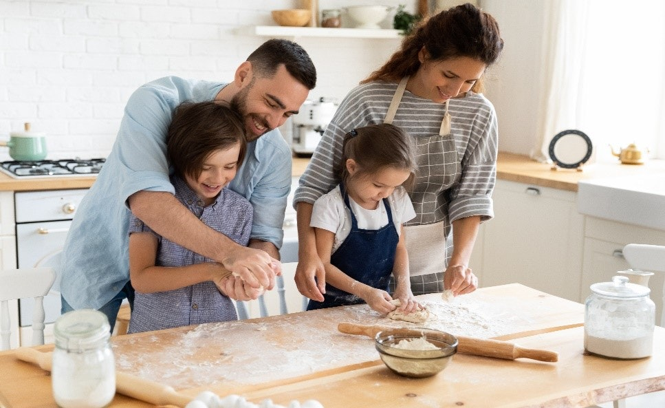Mother and Father teaching children to bake in kitchen