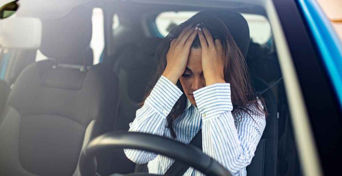 Women sat in the car with her hands on her head, demonstrating that she is stressed and anxious