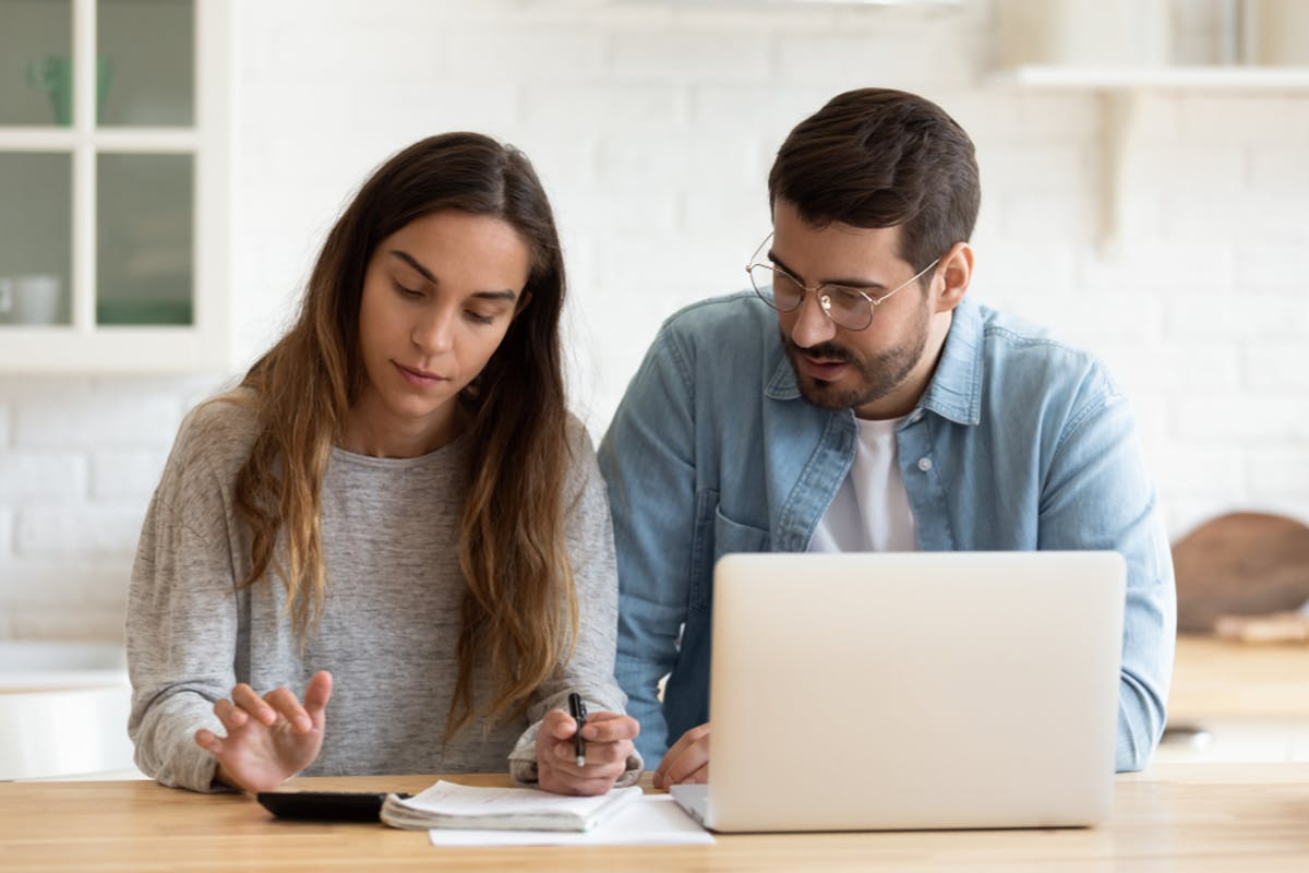 Couple with laptop and calculator trying to asses who are the biggest mortgage lenders in the UK
