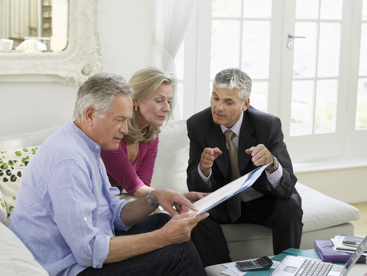 Help your kids on the property ladder – guarantor mortgages and more. Image of older couple discussing becoming mortgage guarantors with mortgage advisor