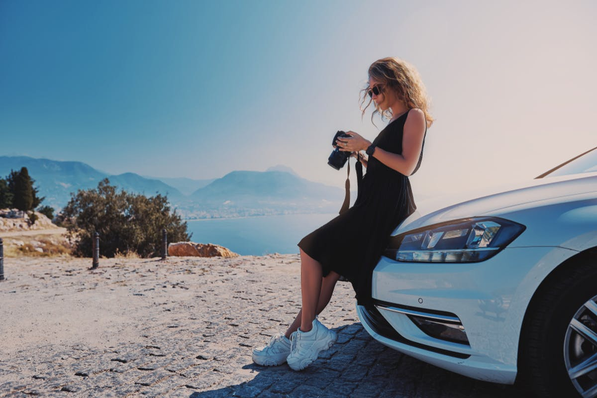 Woman professional photographer standing with dslr camera near her car while travel in Turkey