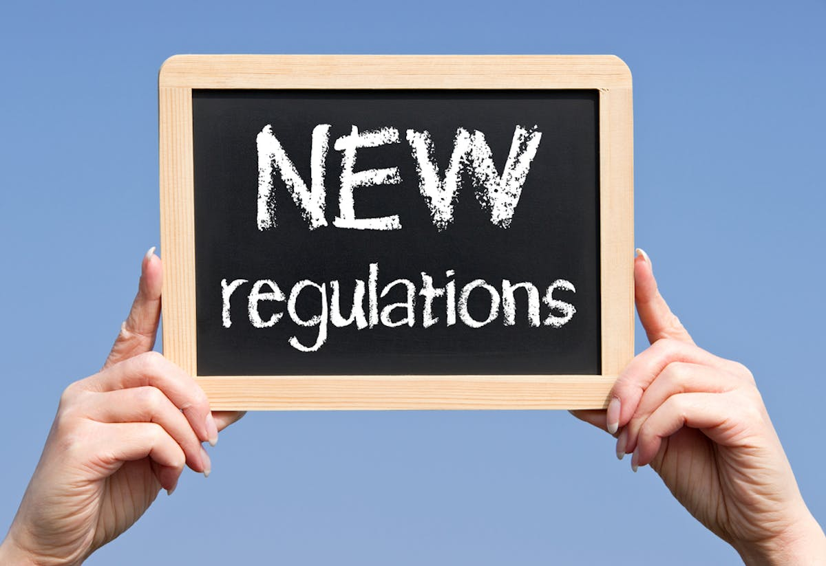 NEW Regulations - hands holding chalkboard with text
