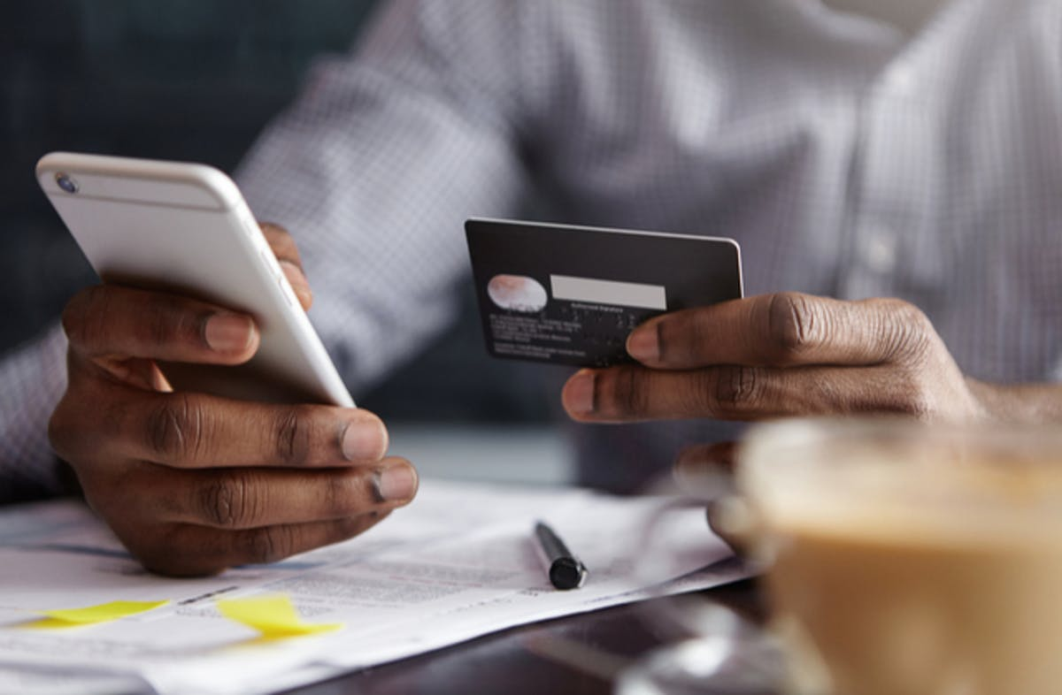 What is PPI image 2 man using phone and credit card