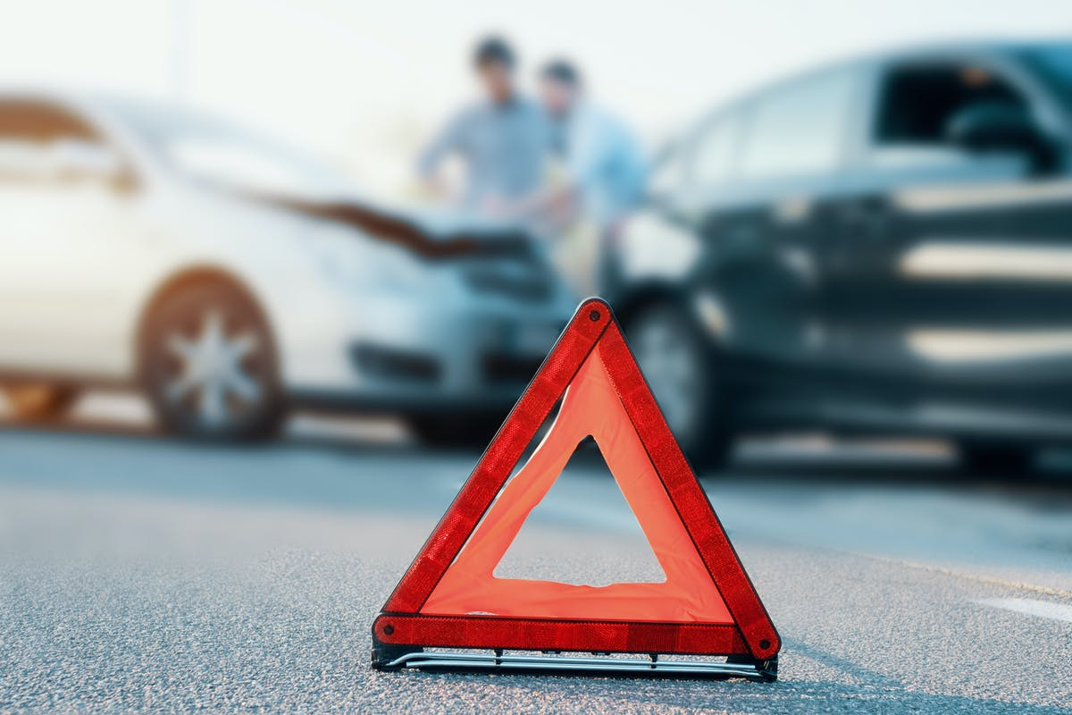 Two cars in the road following and accident or crash, red warning triangle in front of them