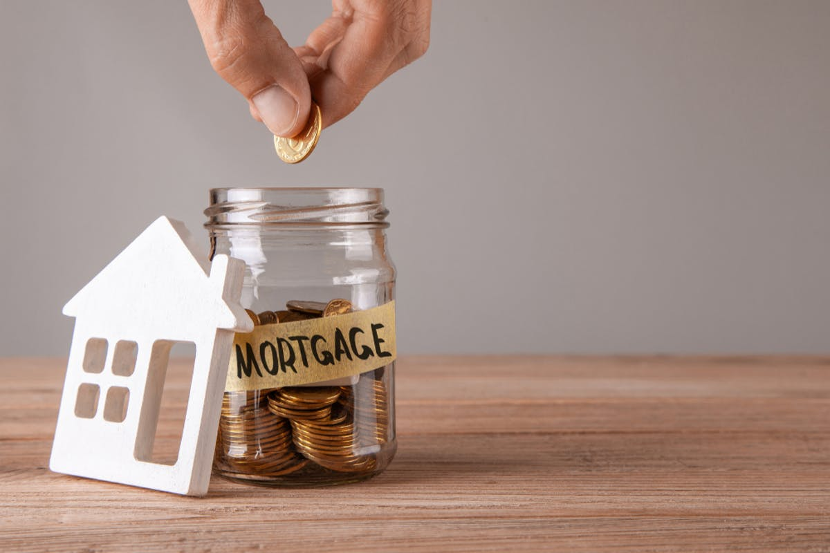 How to save for a mortgage deposit. Image of someone dropping coins in a jar labelled mortgage