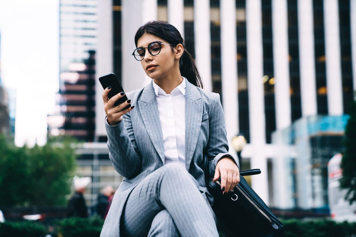 Professional woman using phone in front of office