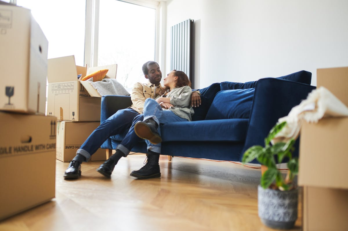 Young couple surrounded by boxes after porting their mortgage