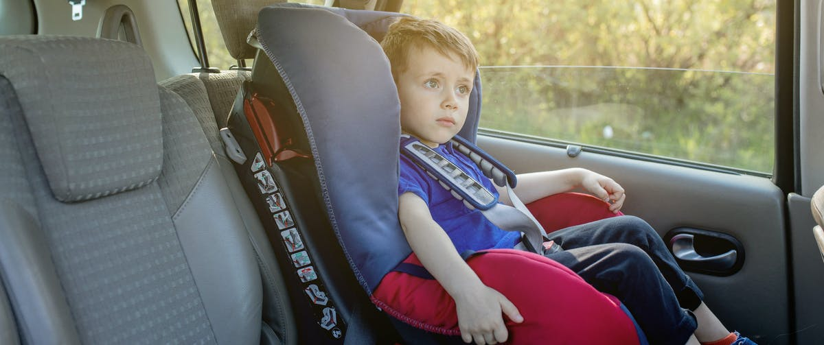 Child in car seat in back of car