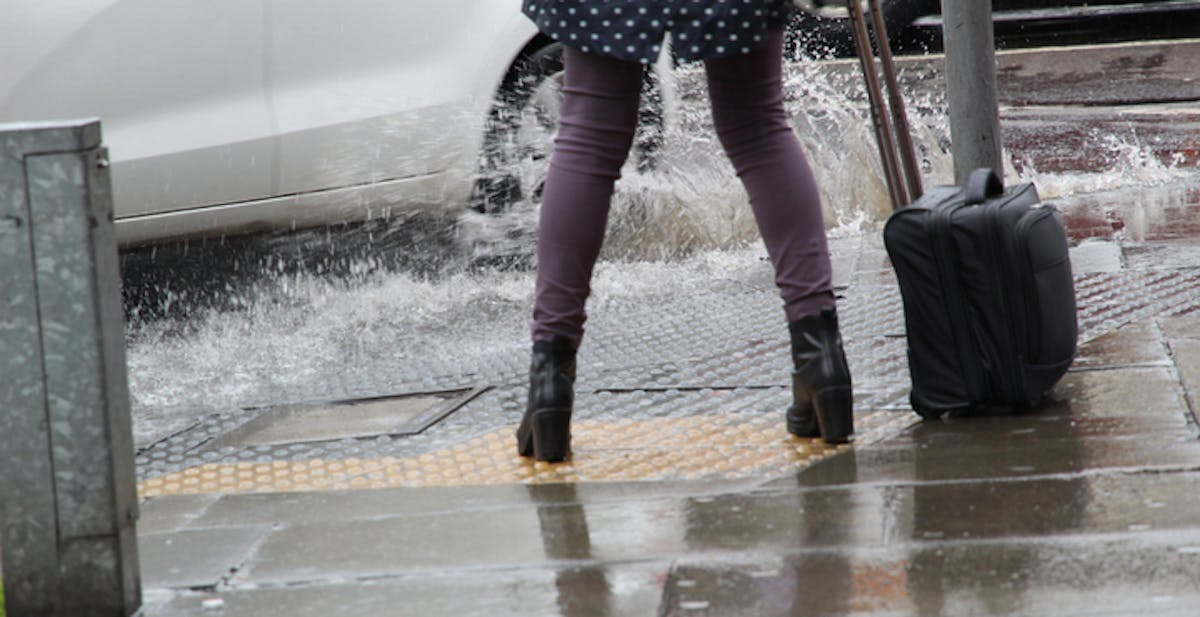 Pedestrian getting splashed by a puddle
