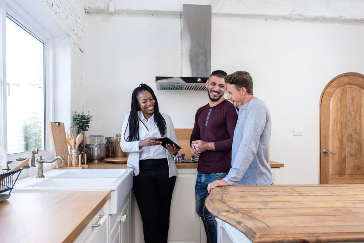 Woman showing young couple around a shared ownership property