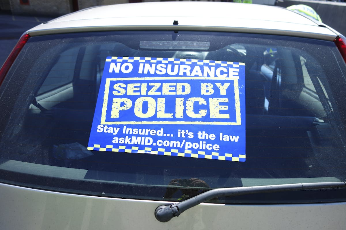 Police no-insurance seizure notice on a car's back window.
