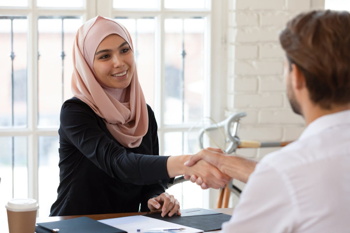 Islamic business lady signing an agreement for an Islamic / halal mortgage