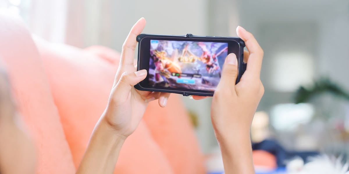 girl playing an online game on her mobile using upload speeds