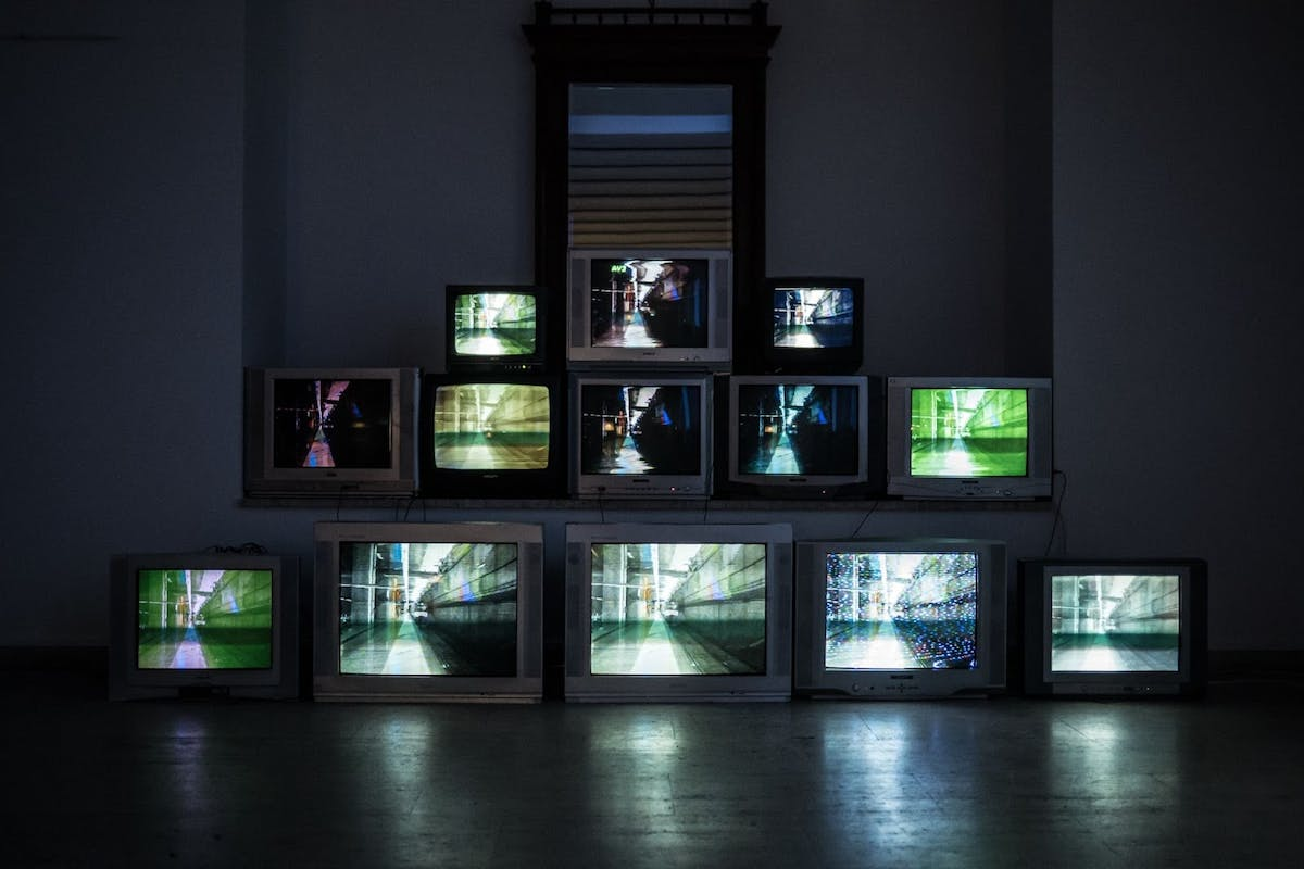 Picture of TV and computer screens stacked in a pyramid formation