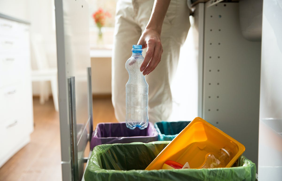Man recycling plastic bottle at home.