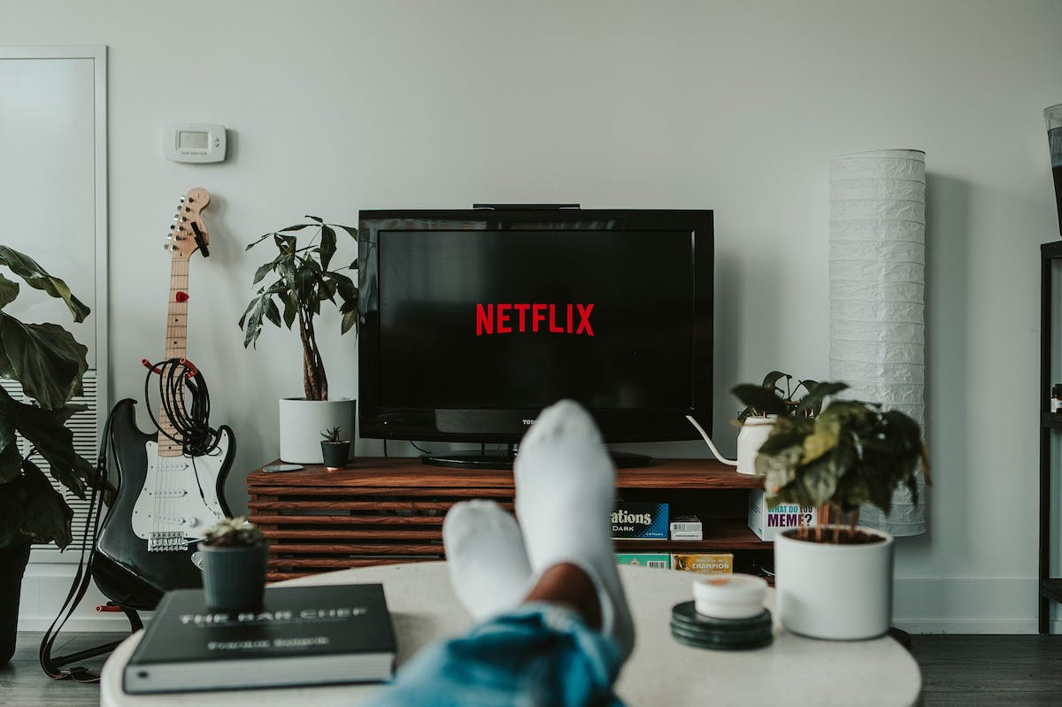 Person feet lying on the sofa whilst watching netflix