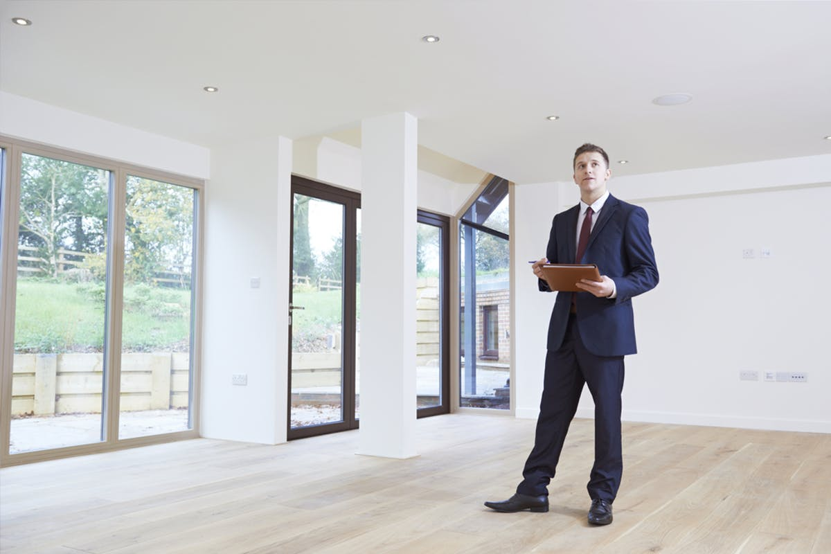 House valuation - how to get a house valuation. Image of an estate agent valuing a property