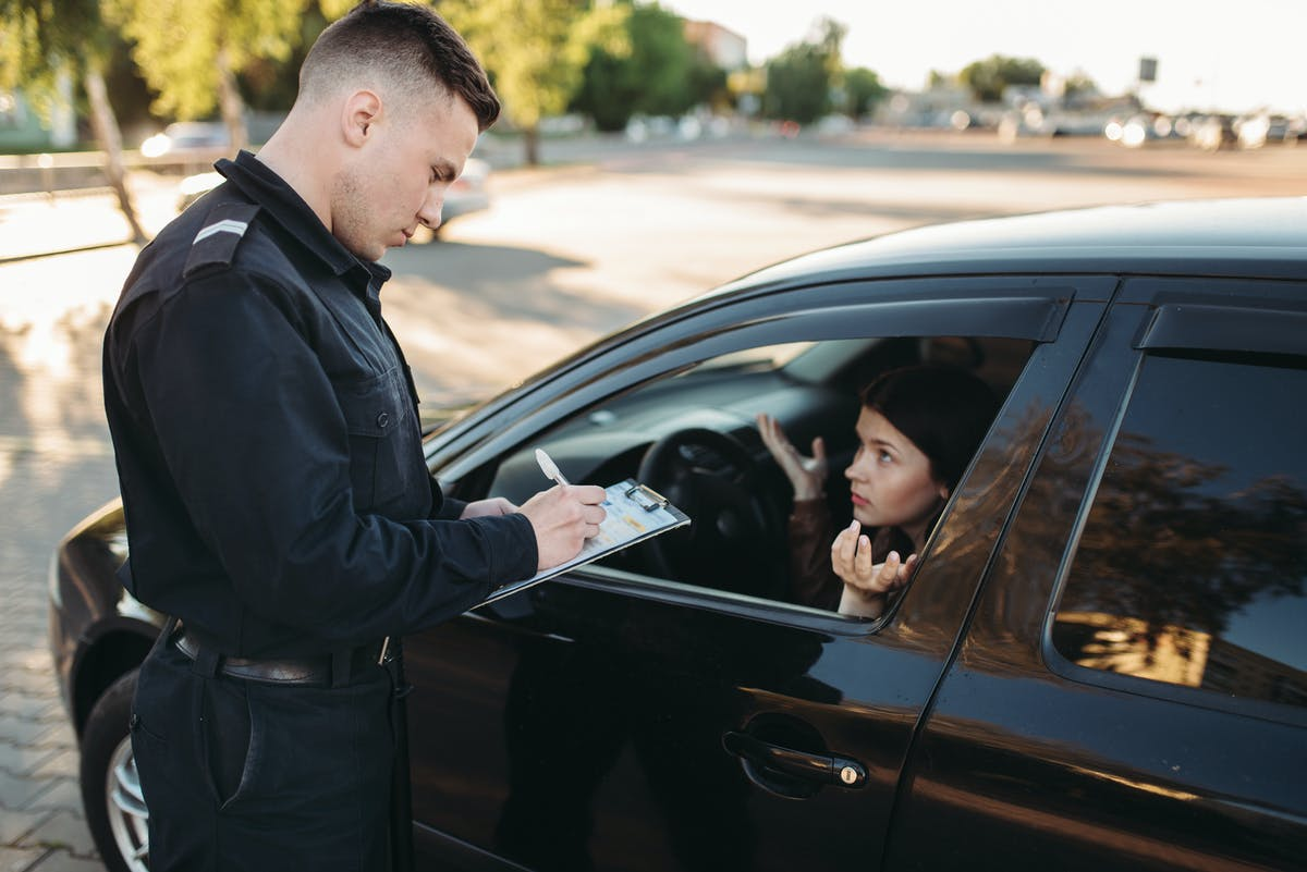 Officer giving woman a ticket in a black car.