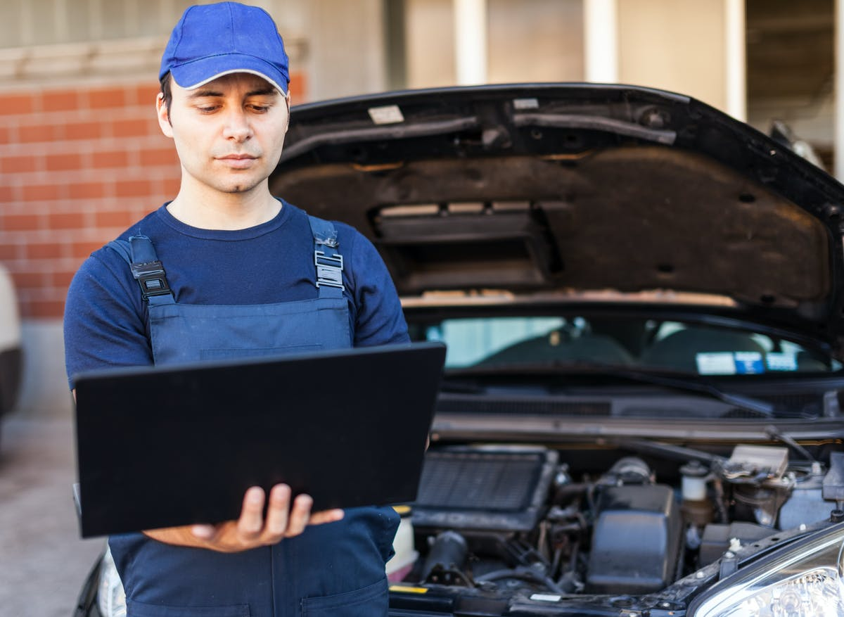 Professional mechanic using a laptop computer to check a car engine