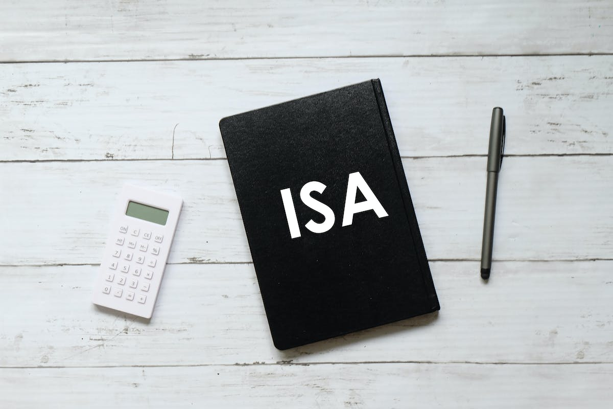 Pen and notebook written with ISA (individual saving account) on white wooden background.