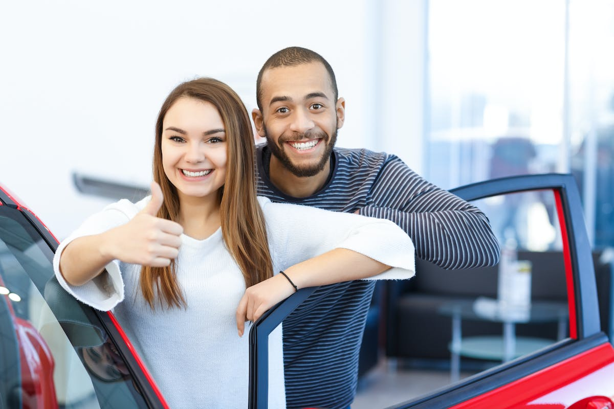 Couple checking out a new car at the dealership looking into vehicle at the salon international interracial buying car relationship concept N