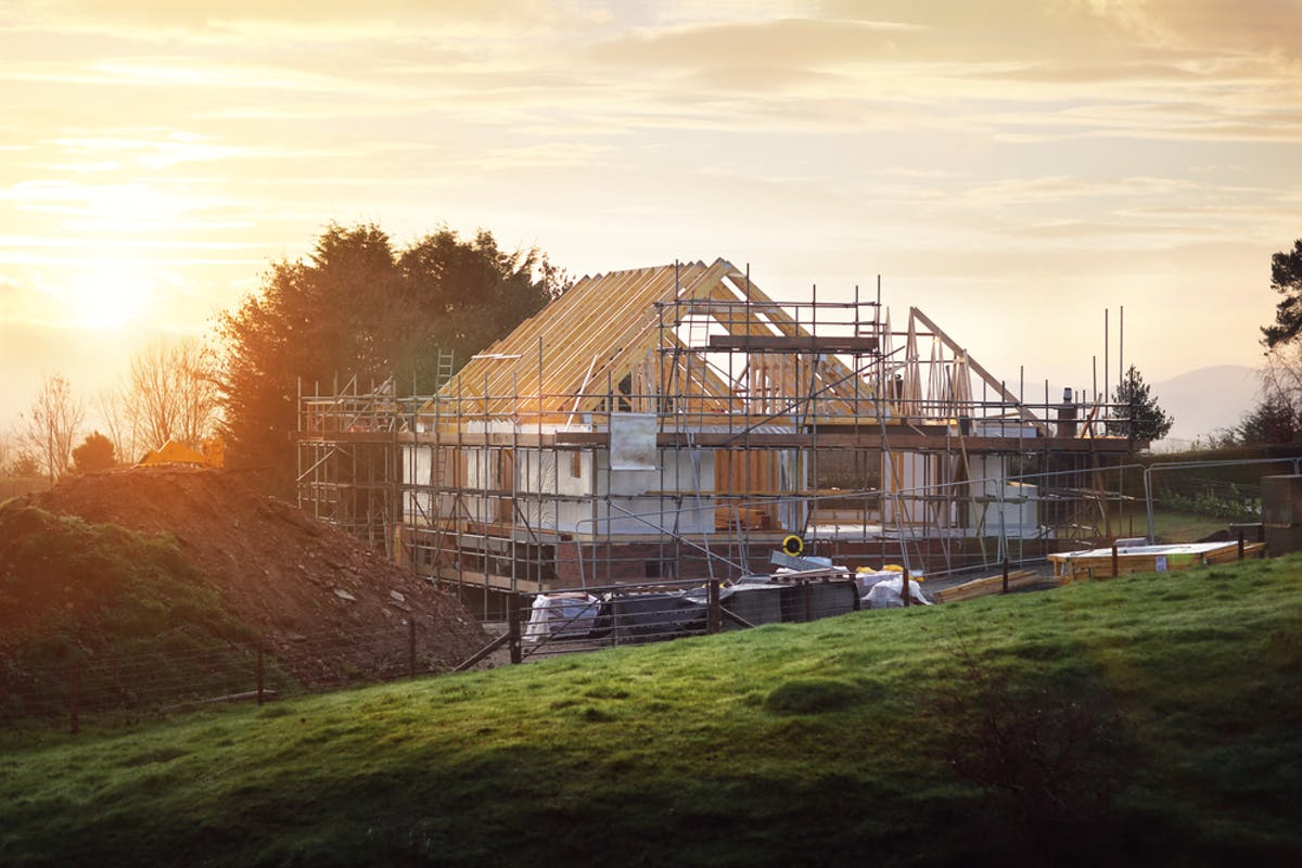 How to build your own home. Part-built house with scaffold in countryside setting.